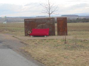Diese Tafel markiert den nordöstlichsten Punkt Frankfurts und erklärt, warum man auf dem Weg von Kiev nach Santiago genau hier vorbei kommt. Die Pilger werden allerdings nicht immer mit einer roten Couch empfangen. Die stand nur 2012 mal für ein paar Tage da.